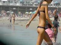 Стройная девушка в черном купальнике прогуливается по пляжу
