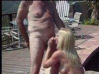 Зрелая пара развлекается под солнышком у бассейна