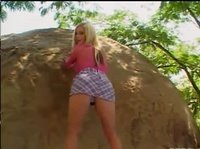 Молоденькая блондинка ласкает свое тело на природе